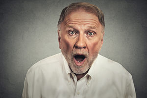 Portrait of a shocked stunned senior man with wide open mouth isolated on gray wall background